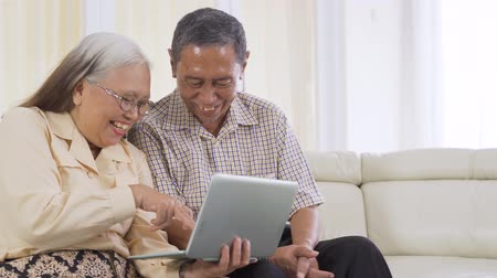 成熟 : Happy senior couple using a laptop computer together while sitting on the sofa at home. Shot in 4k resolution