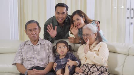 feliz : Group of happy three generation family sitting on the sofa while smiling at the camera. Shot in 4k resolution Stock Footage