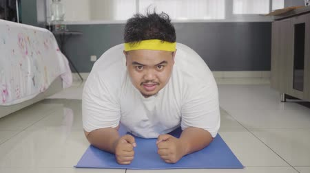 sakk : Young overweight man doing push up or plank exercise on th yoga mat at home. Shot in 4k resolution