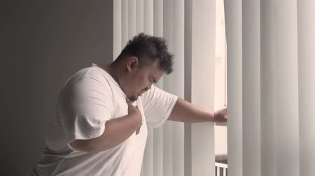 sudden : Overweight man feels heart attack while standing near the window at home. Shot in 4k resolution