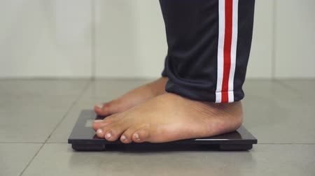 nadváha : Closeup of overweight man feet standing on the weight scale at home. Shot in 4k resolution Dostupné videozáznamy