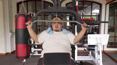 упитанность : Overweight man doing workout on weightlifting machine at fitness center. Shot in 4k resolution