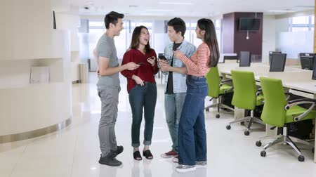 fulllength : Group of happy workers standing in the office while using mobile phone. Shot in 4k resolution Stock Footage