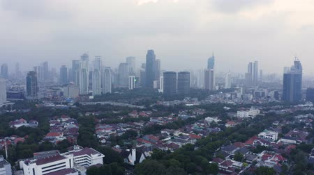 backwards : JAKARTA, Indonesia - May 23, 2019: Aerial view of Jakarta cityscape with residential buildings and skyscrapers background on misty morning. Shot in 4k resolution from a drone flying backwards Stock Footage