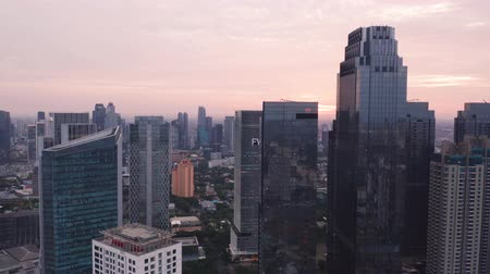 flying upwards : JAKARTA, Indonesia - May 23, 2019: Beautiful aerial Jakarta skyline with silhouette of modern skyscrapers and sunrise background. Shot in 4k resolution from a drone flying upwards Stock Footage