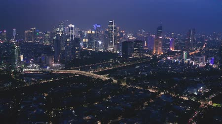 central business district : JAKARTA, Indonesia - May 23, 2019: Aerial Jakarta cityscape with silhouette of residential houses and skyscrapers at night. Shot in 4k resolution from a drone flying backwards
