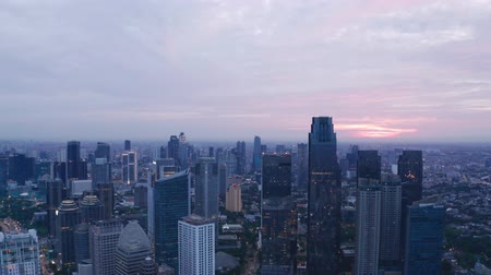 flying upwards : JAKARTA, Indonesia - May 23, 2019: Aerial view of silhouette of modern skyscrapers in Jakarta financial district at sunrise. Shot in 4k resolution from a drone flying upwards Stock Footage
