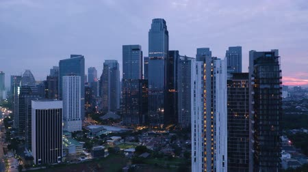 flying upwards : JAKARTA, Indonesia - May 23, 2019: Beautiful aerial view of skyscrapers in Jakarta Central Business District at dawn. Shot in 4k resolution from a drone flying upwards