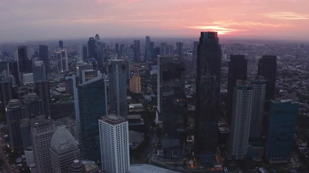 верный : JAKARTA, Indonesia - May 23, 2019: Beautiful aerial view of sunrise with silhouette of skyscrapers in Jakarta Central Business District. Shot in 4k resolution from a drone flying from right to left Стоковые видеозаписи