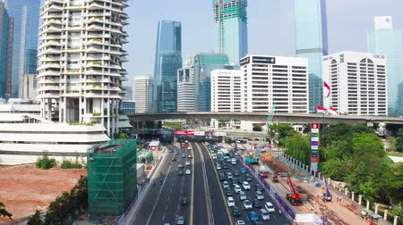 backwards : JAKARTA, Indonesia - May 27, 2019: Aerial view of Sudirman street with traffic jam and modern office buildings background. Shot in 4k resolution from a drone flying backwards