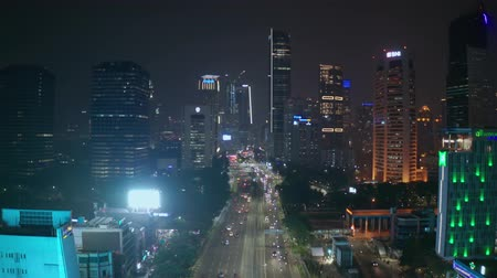 flying upwards : JAKARTA, Indonesia - May 27, 2019: Beautiful aerial view of nighttime with highway and skyscrapers background. Shot in 4k resolution from a drone flying upwards Stock Footage