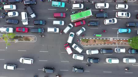 flying upwards : JAKARTA, Indonesia - May 27, 2019: Top down view of crowded cars moving slowly on street u-turn at rush hour. Shot in 4k resolution from a drone flying upwards Stock Footage