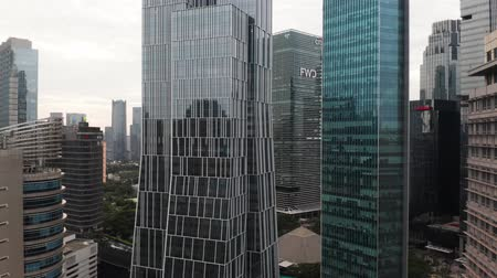 szemléltető : JAKARTA, Indonesia - May 27, 2019: Aerial view of modern office buildings with glass windows in business district. Shot in 4k resolution from a drone flying upwards Stock mozgókép
