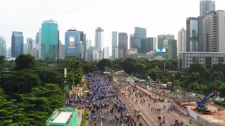 rua : JAKARTA, Indonesia - May 27, 2019: Aerial view of crowded people enjoy outdoor activities during the car free day at Sudirman street. Shot in 4k resolution from a drone flying forwards