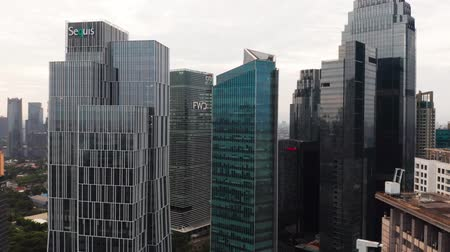 митрополит : JAKARTA, Indonesia - May 27, 2019: Aerial scenery of skyscrapers in business district with glass windows. Shot in 4k resolution from a drone flying backwards Стоковые видеозаписи