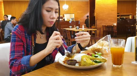 comida japonesa : JAKARTA, Indonesia - May 27, 2019: Young woman enjoying her lunch on the table in the restaurant Vídeos