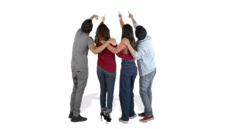 bum : Back view group of young people pointing and looking up in the studio, isolated on white background. Shot in 4k resolution