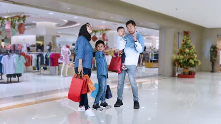 sourozenci : Happy young parents and their children standing in shopping center while holding shopping bags. Shot in 4k resolution Dostupné videozáznamy