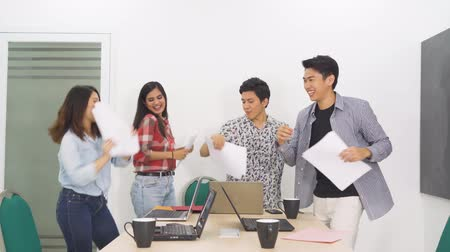 indonésio : Successful casual business people celebrating their success by dancing and throwing paperwork in the office room. Shot in 4k resolution Vídeos
