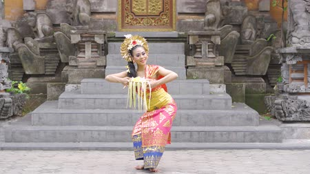vítejte : Beautiful balinese dancer posing in the temple while wearing traditional costume and holding frangipani flower. Shot in 4k resolution Dostupné videozáznamy