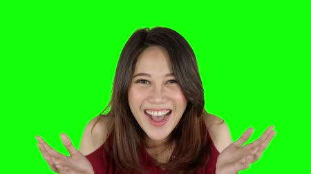 tela : Excited young Asian woman looking at the camera in the studio. Shot in 4k resolution with green screen background