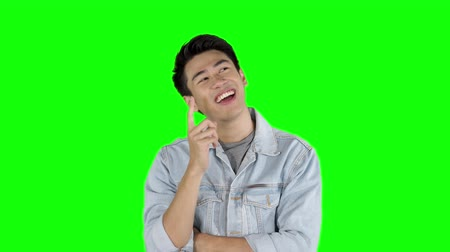 çözmek : Young Asian man thinking in the studio and looks getting an idea. Shot in 4k resolution with green screen background