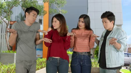 nejistota : Group of doubtful college student shrugging their shoulders outdoors. Shot in 4k resolution
