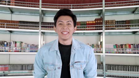 hajtogatott : Handsome man with casual clothes smiling at the camera in the library. Shot in 4k resolution Stock mozgókép