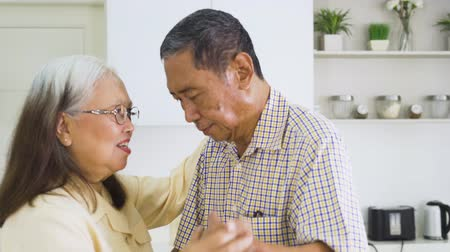 emeryt : Happy senior couple dancing together while enjoying leisure time in the kitchen at home. Shot in 4k resolution