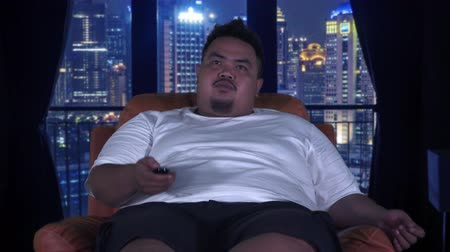 ленивый : Overweight young man sitting on the sofa while watching TV at night in apartment. Shot in 4k resolution Стоковые видеозаписи