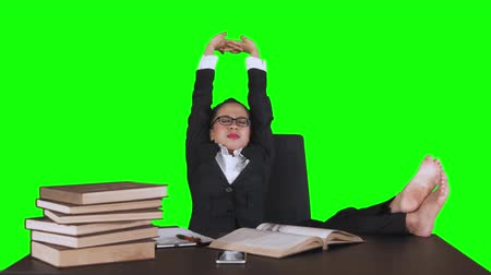 книга : Attractive young businesswoman sitting on office chair while daydreaming with books on table. Shot in 4k resolution with green screen background Стоковые видеозаписи