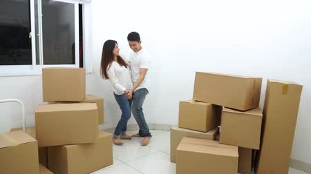 kutu : Happy couple with cardboard boxes dancing in new house. Shot in 4k resolution