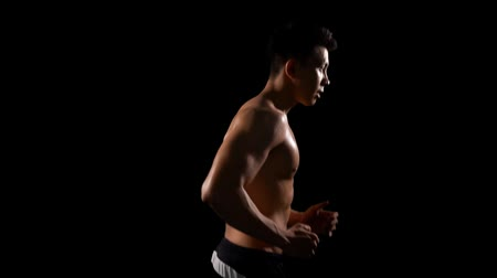 donker : Slow motion of handsome muscular man doing workout by running in place. Shot in the studio on dark background Stockvideo
