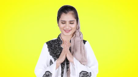 perdão : Beautiful young Asian muslim woman smiling at the camera and showing greeting gesture in the studio. Shot in 4k resolution