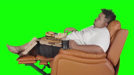 жадный : Side view of obese man eating junk foods and drinking cola while sitting on the sofa and watching TV. Shot in 4k resolution with green screen background