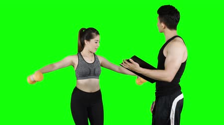 panoya : Pretty young woman exercising with dumbbells and her personal trainer. Shot in 4k resolution with green screen background