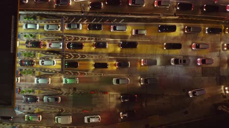 queue : Top down view of cars in lines to enter toll gateway on rush hour at night in Jakarta city, Indonesia. Shot in 4k resolution from a drone