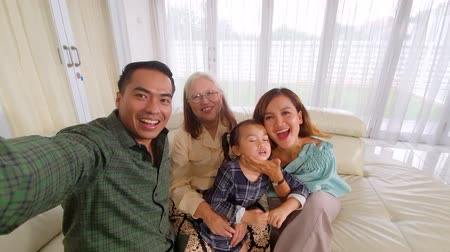 an : Happy three generation family making a video while smiling at the camera in the living room at home. Shot in 4k resolution