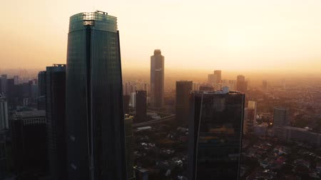flying upwards : JAKARTA, Indonesia - June 25, 2019: Aerial view of silhouette of modern office buildings and orange sky on foggy morning. Shot in 4k resolution from a drone flying upwards Stock Footage