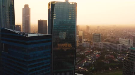 flying upwards : JAKARTA, Indonesia - June 25, 2019: Aerial landscape of misty morning with silhouette of modern office buildings and air pollution smoke. Shot in 4k resolution from a drone flying upwards Stock Footage