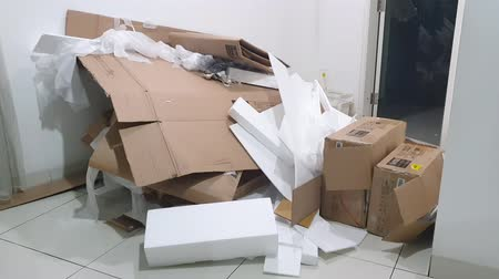 usado : JAKARTA, Indonesia - June 25, 2019: Pile of used cardboard and styrofoam at home. Shot in 4k resolution