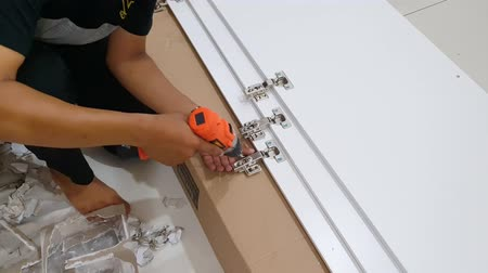 монтаж : JAKARTA, Indonesia - June 25, 2019: Repairman mounting the screw on a new cabinet furniture with a drill at home. Shot in 4k resolution