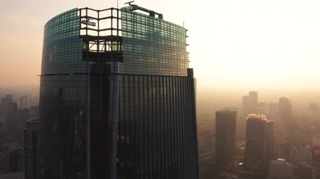 flying upwards : JAKARTA, Indonesia - June 25, 2019: Aerial view of silhouette of modern skyscrapers with fog of air pollution on the morning. Shot in 4k resolution from a drone flying upwards