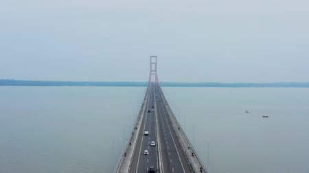 madura : Beautiful aerial view of Suramadu bridge with fast traffic on foggy morning from a drone flying forwards. Shot in 4k resolution