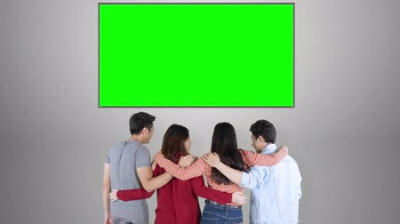csikk : Back view of young people standing in the studio while embracing to each other while looking at empty copy space with green background. Shot in 4k resolution
