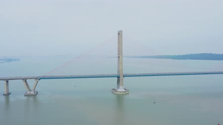 süspansiyon : Beautiful aerial view of Suramadu bridge with fast traffic on foggy morning at Madura strait. Shot in 4k resolution from a drone flying from right to left