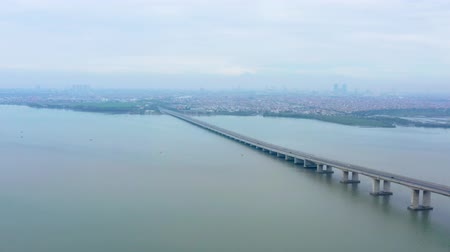 madura : Aerial view of Suramadu bridge with Madura strait background and Surabaya city on misty morning. Shot in 4k resolution from a drone flying forwards