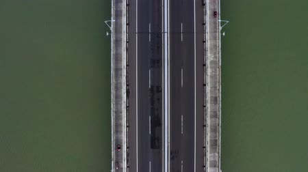 the suspension bridge : Top down view of Suramadu bridge with quiet traffic on the morning at Madura strait. Shot in 4k resolution from a drone flying backwards