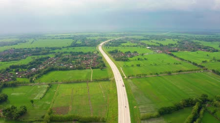 backwards : Beautiful aerial view of Trans-Java toll road between green rice fields and village. Shot in 4k resolution from a drone flying backwards Stock Footage