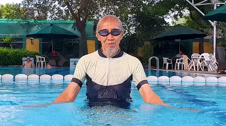 indonésio : Senior man playing water on the swimming pool while wearing swimwear and goggles. Shot in 4k resolution